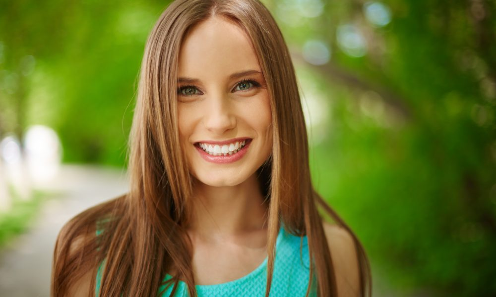 Portrait of smiling girl looking at camera outdoors