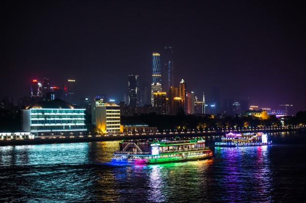 vista-nocturna-de-la-ciudad-con-barcos-en-el-agua_1137-98