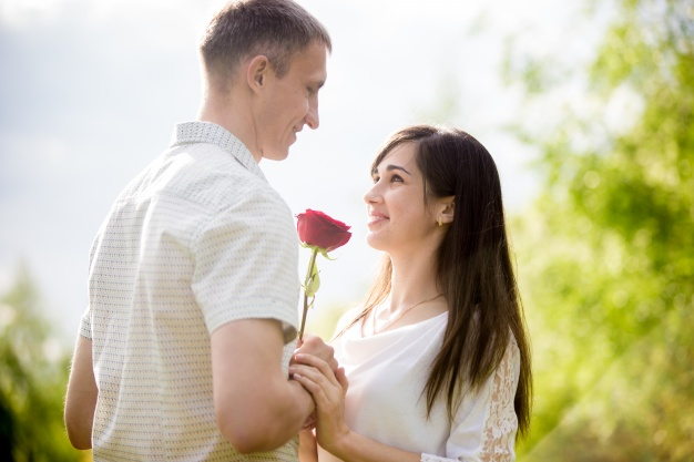 tio-romantico-dandole-una-flor-a-su-novia-sonriente_1163-605