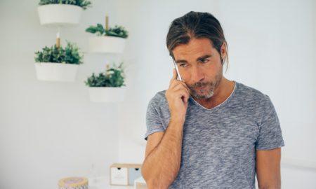 primer-plano-de-hombre-de-negocios-usando-su-telefono-con-plantas-detras_23-2147577294
