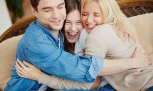 familia-alegre-abrazandose-en-el-sofa_1098-3601