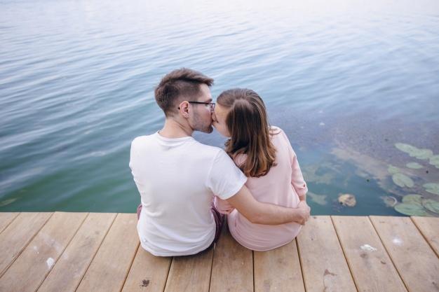 pareja-besandose-sentados-en-un-muelle-de-madera_1157-1383