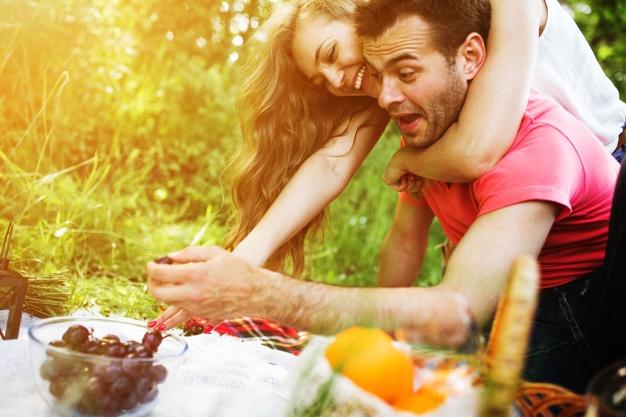 pareja-sonriente-comiendo-uvas_1153-1401