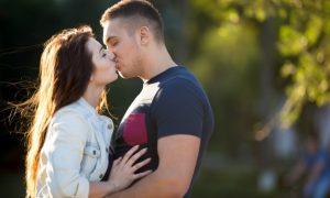 pareja-joven-besandose-en-un-dia-soleado_1163-842