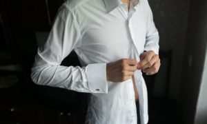 primer-plano-de-novio-abrochandose-la-camisa_1153-444