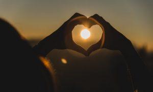 manos-haciendo-la-forma-de-un-corazon-con-el-sol-enmedio_23-2147596674