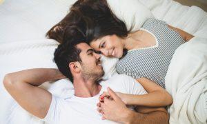 pareja-tumbada-en-la-cama-agarrada-de-la-mano-y-mirandose-a-los-ojos_23-2147596021
