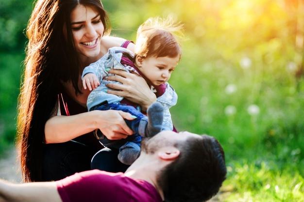 mujer-con-un-bebe-en-brazos-mientras-su-novio-la-mira_1153-2060