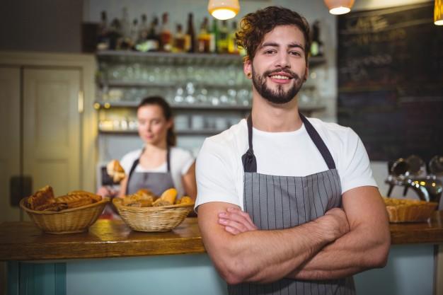 sonriendo-camarero-de-pie-con-los-brazos-cruzados-en-la-cafeteria-c_1170-606