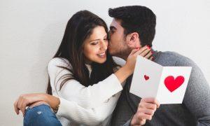 hombre-besando-a-una-chica-en-la-cara-y-esta-lee-una-tarjeta-postal_23-2147595876