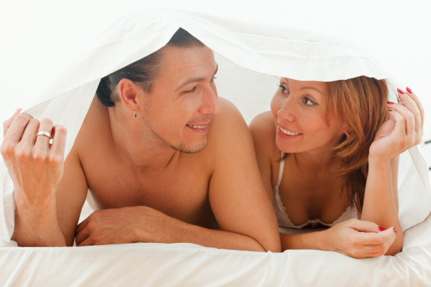 feliz-pareja-jugando-en-la-cama_1398-4244