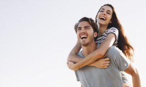 novio-sonriente-llevando-novia-sonriente-por-la-playa_23-2147641346