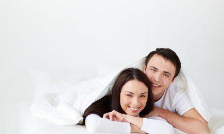 pareja-sonriente-tumbada-en-la-cama_1098-3788
