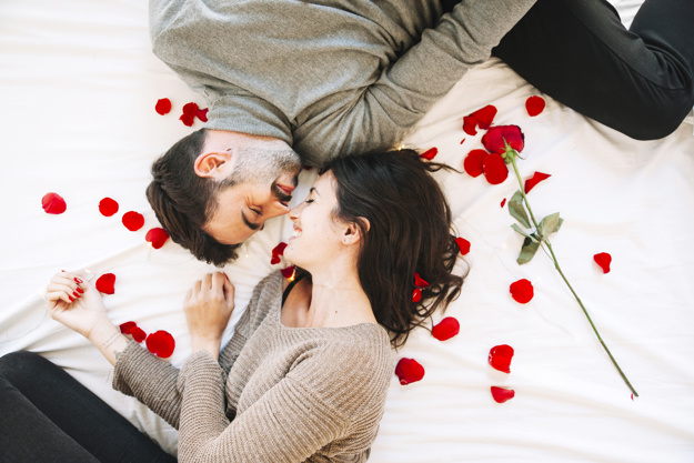 pareja-alegre-tocar-narices-en-petalos-de-rosa_23-2147744571