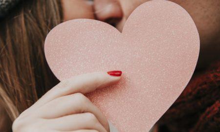 pareja-besandose-y-sosteniendo-corazon_23-2147736074