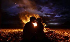 pareja-de-besos-se-sienta-ante-una-chimenea-en-la-playa_1304-5411