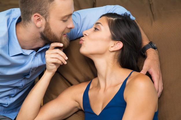 joven-pareja-apasionada-acostado-en-el-sofa-y-los-besos_1262-1025