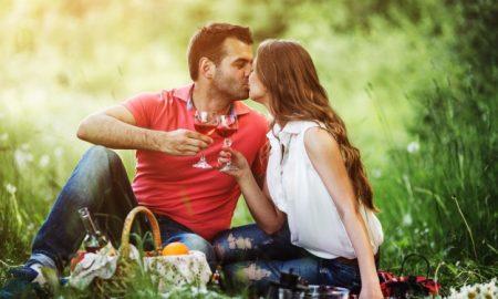 pareja-besandose-y-sujetando-unas-copas-de-vino_1153-1395