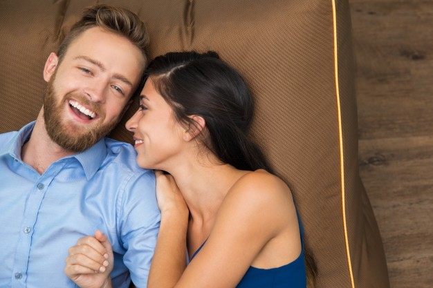 sonriente-joven-pareja-disfrutando-acostado-en-el-sofa_1262-1178