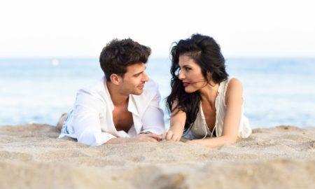 pareja-tumbada-en-la-arena-de-la-playa_1139-572