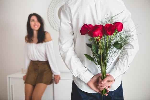 chica-sujetando-globos-con-forma-de-corazon-mientras-su-novio-tiene-un-ramo-de-rosas-en-la-espalda_23-2147595978