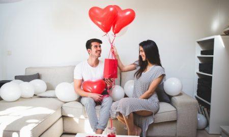 mujer-entregando-a-su-novio-globos-y-una-bolsa-roja_23-2147596037