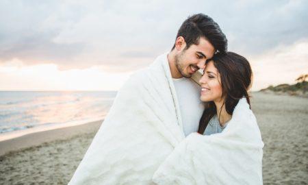 pareja-enamorada-sentada-en-una-playa-cubierta-por-una-manta-blanca_23-2147595914
