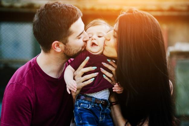 padre-y-madre-besando-a-un-bebe-en-las-mejillas_1153-2054