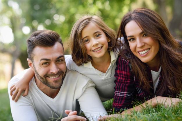 pareja-sonriendo-tumbada-en-el-cesped-con-su-hija_1139-618