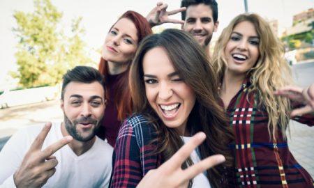 chica-sonriendo-haciendo-una-autofoto-con-sus-amigos-alrededor_1139-593
