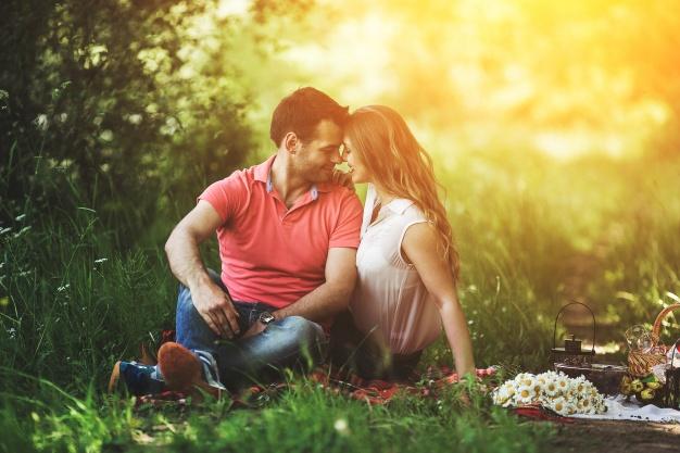 pareja-sentada-en-hierba-mirandose-a-los-ojos_1153-1933