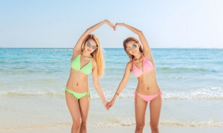 dos-jovenes-asiaticos-morena-mejores-amigos-mirando-a-camara-y-enviarle-aire-beso-tienen-cuerpo-delgado-sexy-vistiendo-bikini-gafas-de-sol-y-joyeria-de-moda-brillante-posando-en-frente-de-la-playa-tr