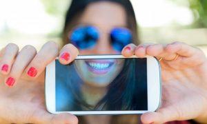 retrato-de-muchacha-hermosa-que-toma-un-selfie-con-el-telefono-movil-en_1301-3497