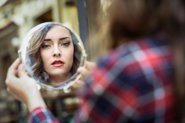 mujer-mirandose-en-un-espejo_1139-519