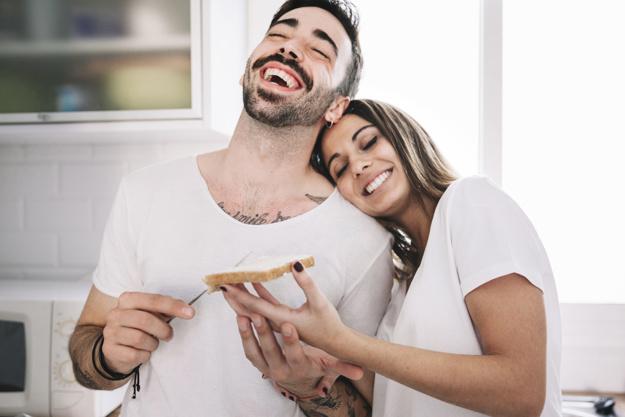 gente-riendo-haciendo-el-desayuno-juntos_23-2147742376
